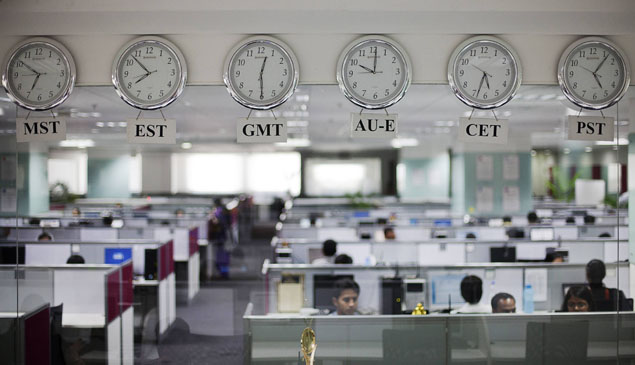 Workers are pictured beneath clocks displaying time zones in various parts of the world at an outsourcing centre in Bangalore