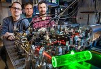An atomic memory (glowing green), made at the Faculty of Physics at the University of Warsaw, can be used to store quantum information in telecomunication purposes. From left to right: Michał Dąbrowski, Radek Chrapkiewicz and Wojciech Wasilewski.